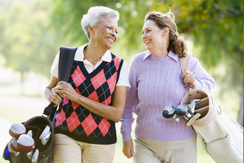 Two women walking and carrying golf clubs